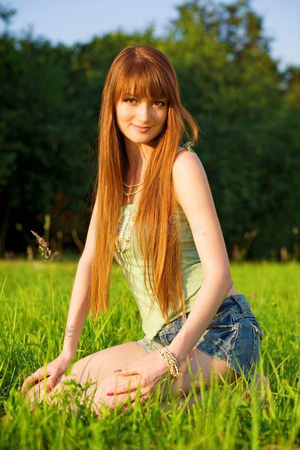 Jonge mooie redhead vrouwenzitting op gras stock foto's