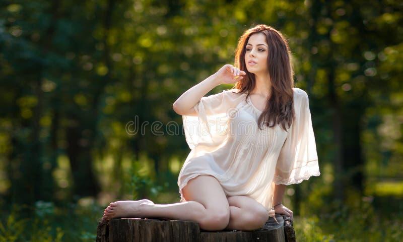 Jonge mooie rode haarvrouw die het transparante witte blouse stellen op een stomp in een groen bos Modieus sexy meisje dragen stock foto's