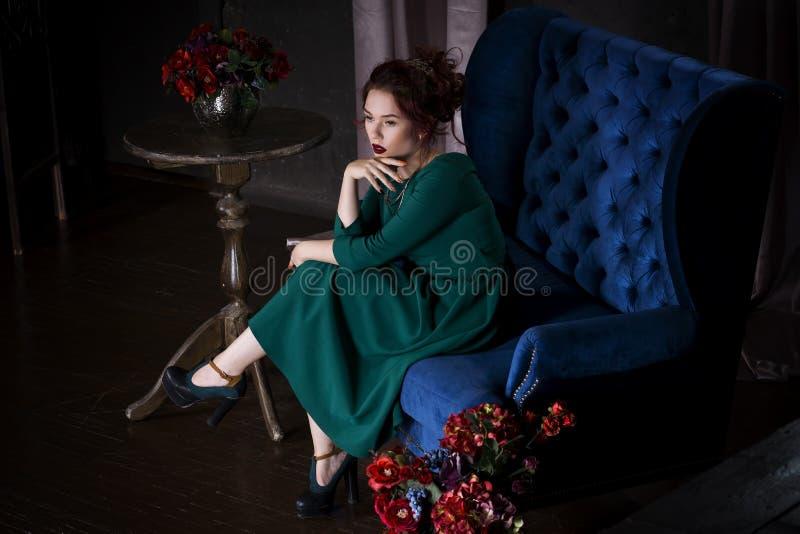 Jonge mooie roodharige Kaukasische vrouw met professionele make-up in het groene kleding stellen op blauwe bank royalty-vrije stock foto's