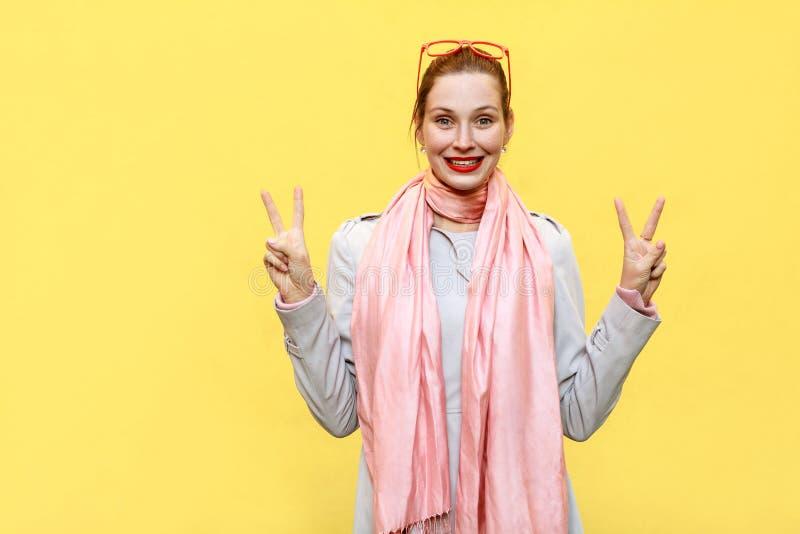 Jonge mooie roodharigevrouw die vredesteken tonen royalty-vrije stock afbeelding