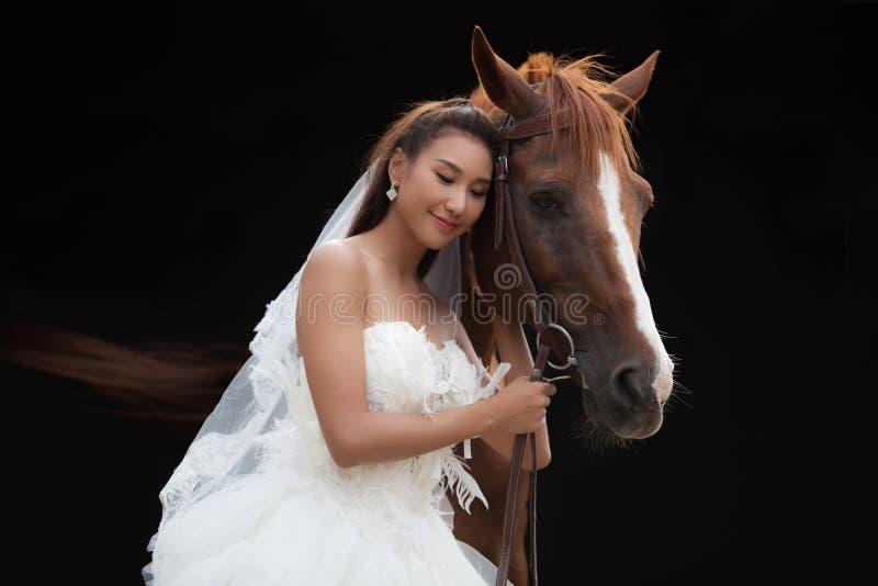 Jonge mooie schoonheidsbruid in het kostuumtribune van het manier witte huwelijk met knap paard op zwarte achtergrond stock foto's