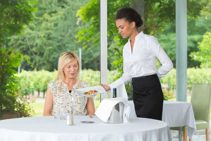 Jonge mooie serveerster die witte dame dienen bij gastronomierestaurant royalty-vrije stock afbeeldingen