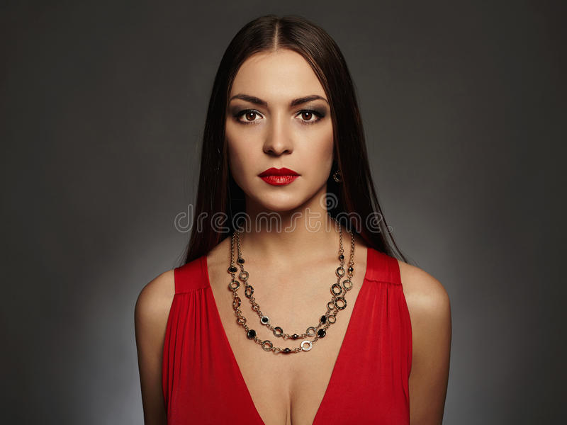 Jonge mooie sexy vrouw Schoonheidsmeisje die juwelen dragen Elegante dame in rode kleding royalty-vrije stock foto's