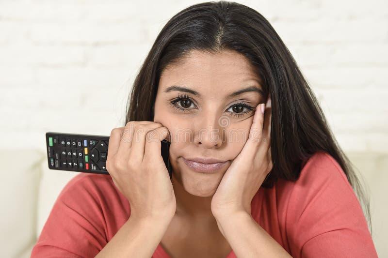 Jonge mooie Spaanse vrouw die thuis vermoeid en bored op televisie letten royalty-vrije stock afbeeldingen