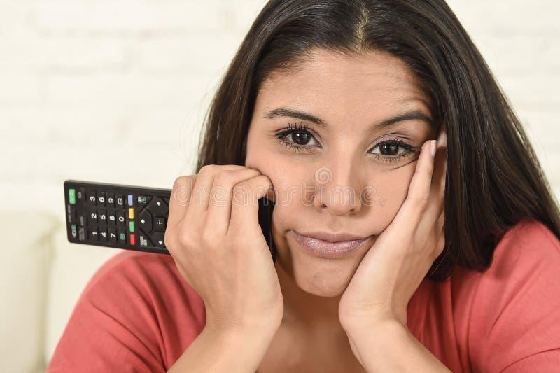 Jonge mooie Spaanse vrouw die thuis vermoeid en bored op televisie letten stock afbeelding