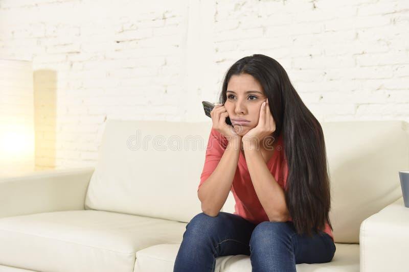 Jonge mooie Spaanse vrouw die thuis vermoeid en bored op televisie letten stock foto's