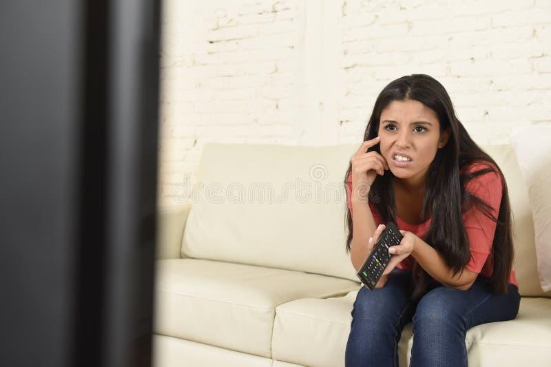 Jonge mooie Spaanse vrouw die thuis vermoeid en bored op televisie letten royalty-vrije stock foto's