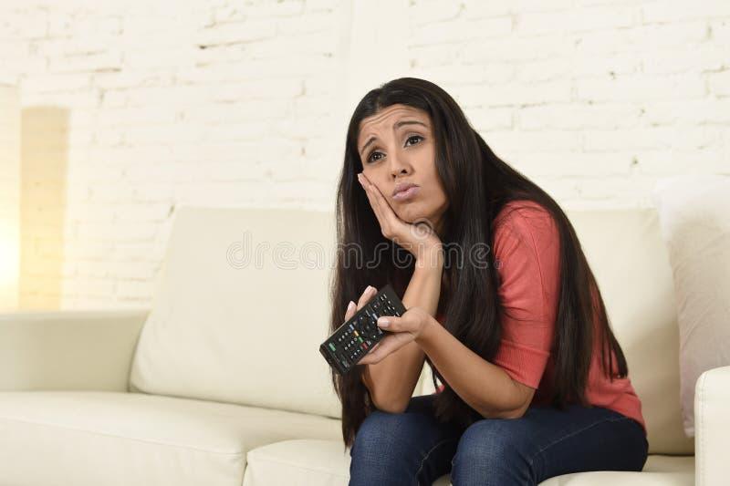 Jonge mooie Spaanse vrouw die thuis vermoeid en bored op televisie letten stock foto