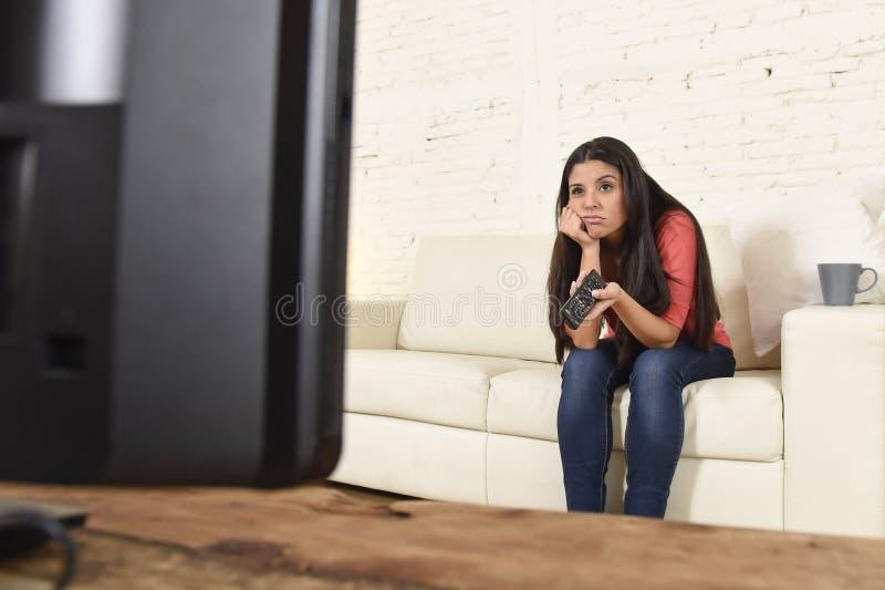 Jonge mooie Spaanse vrouw die thuis vermoeid en bored op televisie letten stock fotografie