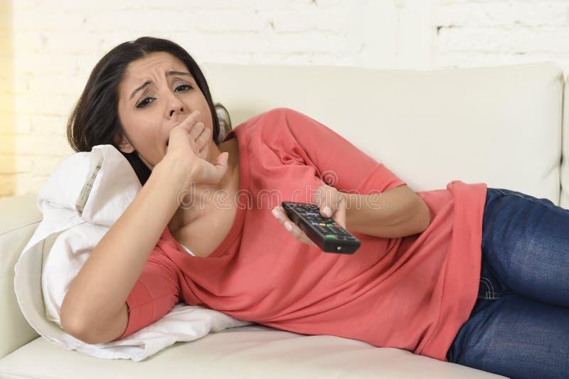 Jonge mooie Spaanse vrouw die thuis vermoeid en bored op televisie letten royalty-vrije stock afbeelding