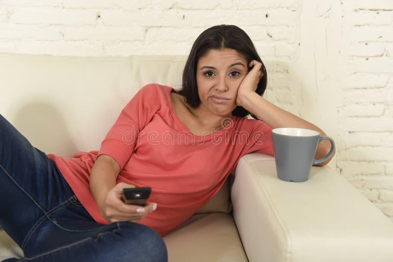 Jonge mooie Spaanse vrouw die thuis vermoeid en bored op televisie letten stock afbeeldingen