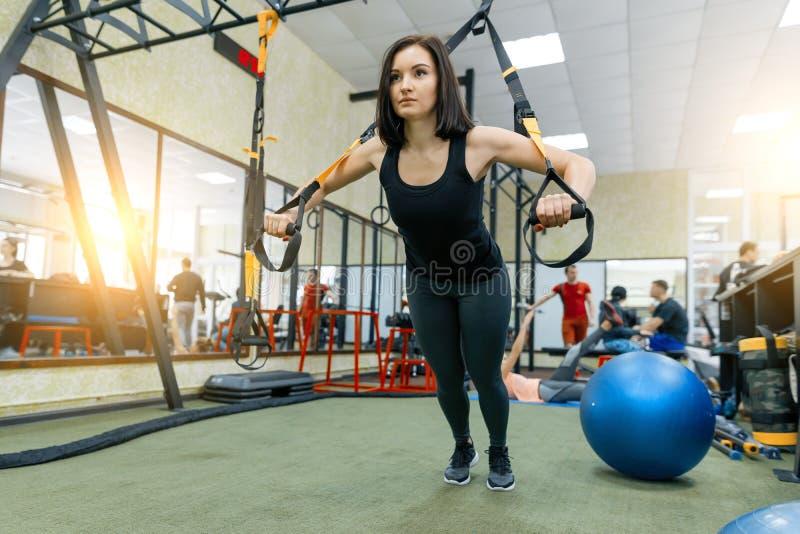 Jonge mooie sportieve vrouw die op het systeem van geschiktheidsriemen in gymnastiek uitoefenen Fitness, sport, opleiding, en gez stock afbeelding