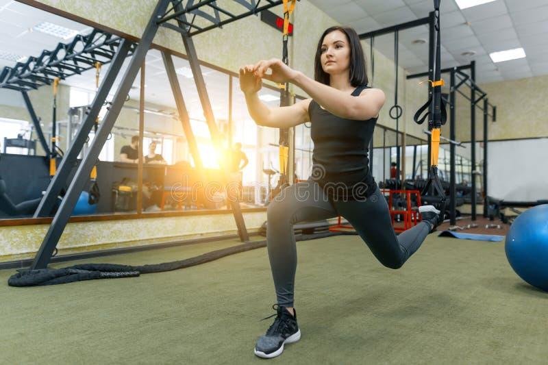 Jonge mooie sportieve vrouw die op het systeem van geschiktheidsriemen in gymnastiek uitoefenen Fitness, sport, opleiding, en gez stock fotografie