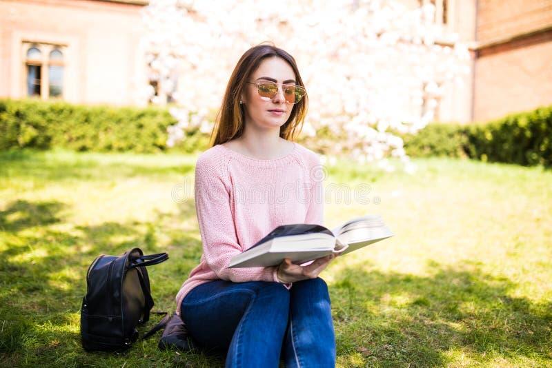 Jonge mooie studente die in de zomerpark een boek op het gras lezen royalty-vrije stock foto