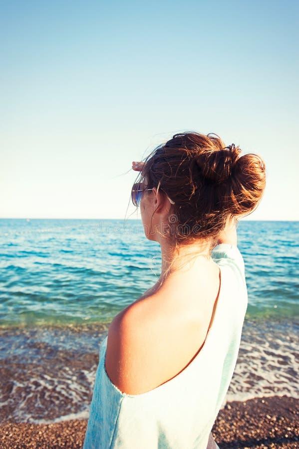 Jonge mooie tiener die vooruit het strand van de Middellandse Zee bekijken stock foto