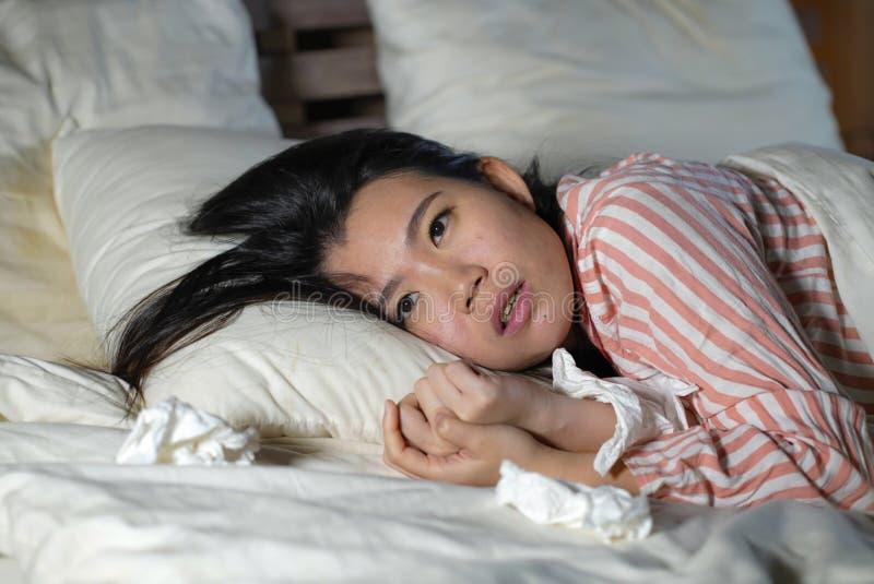 Jonge mooie vermoeide en zieke Aziatische Chinese vrouw die op bed thuis zieken liggen die aan koud griep en temperatuur onwel ge stock afbeelding