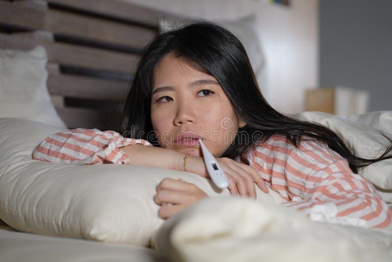 Jonge mooie vermoeide en zieke Aziatische Japanse vrouw die op bed thuis zieken liggen die aan koud griep en temperatuur onwel ge royalty-vrije stock afbeelding