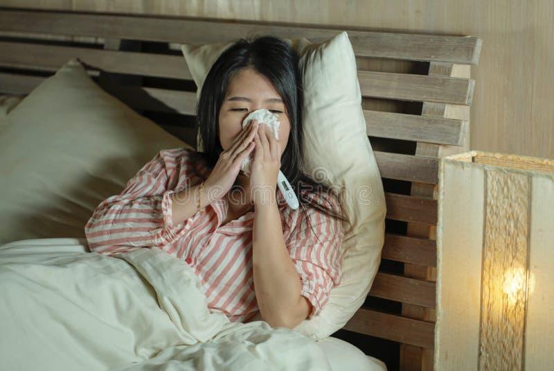 Jonge mooie vermoeide en zieke Aziatische Japanse vrouw die op bed thuis zieken liggen die aan koud griep en temperatuur onwel ge stock afbeelding