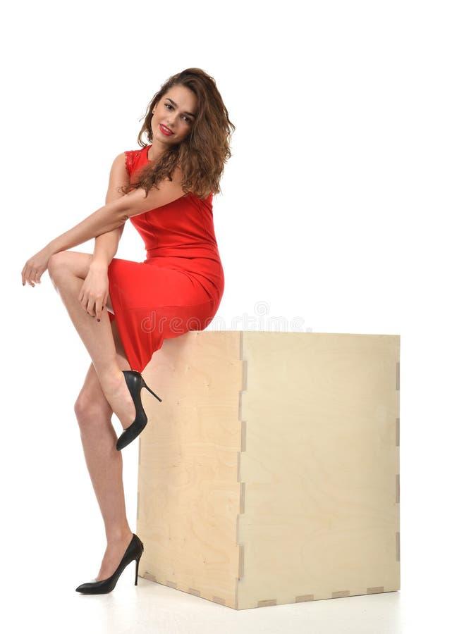 Jonge mooie volledige lichaamsvrouw in rode kleding met grote houten del stock afbeelding