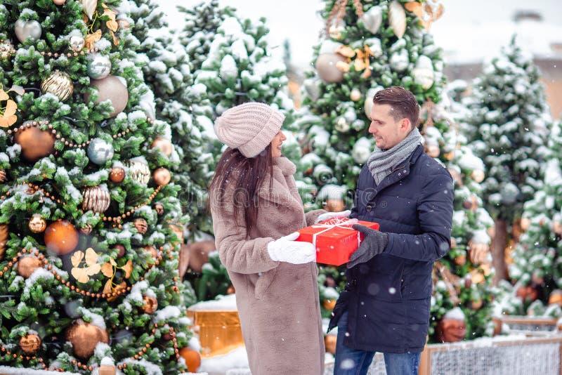 Jonge mooie vrolijke paar het vieren Kerstmis in de stadsstraat en het geven van gift aan elkaar royalty-vrije stock afbeeldingen