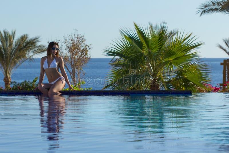 Jonge mooie vrouw aan de kant van zwembad stock afbeelding