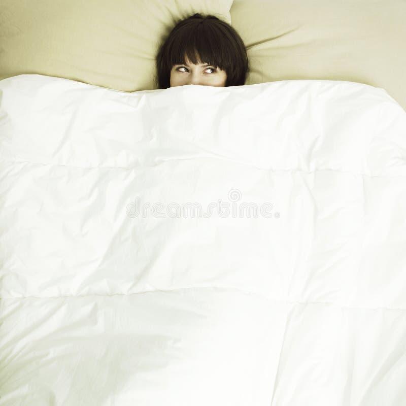 Jonge mooie vrouw in bed stock fotografie