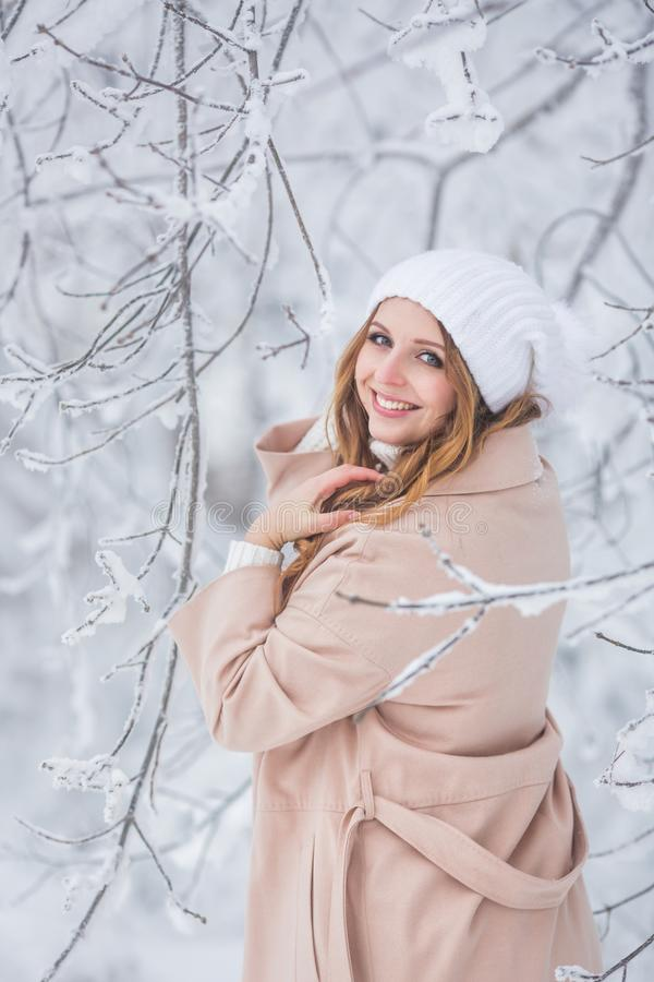 Jonge mooie vrouw in beige ress dichtbij de winterbomen - Achtermening royalty-vrije stock foto