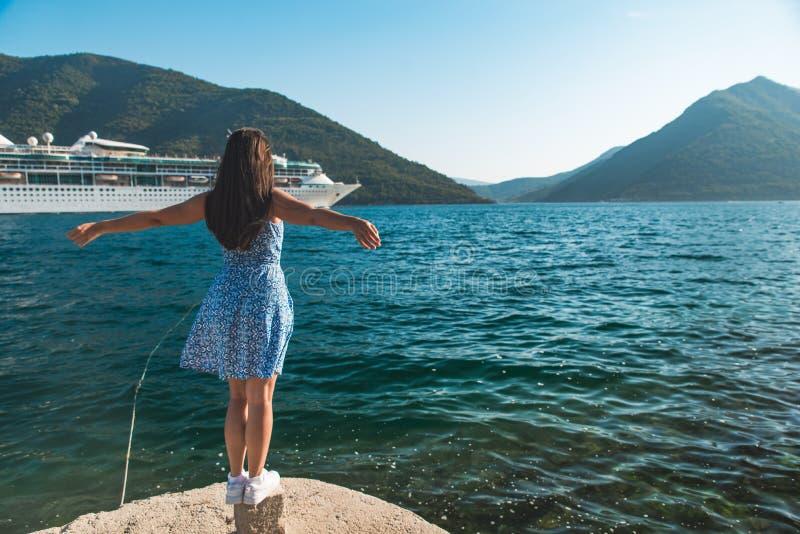 Jonge mooie vrouw bij de rand van het dok met mooie mening van bergen en overzees met cruisevoering stock foto