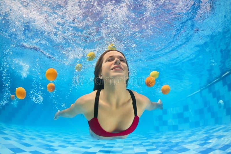 Jonge mooie vrouw in bikini zwemmen onderwater in pool stock afbeeldingen