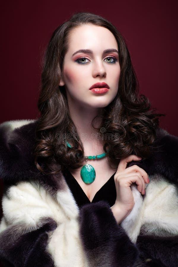 Jonge mooie vrouw in bontjas en met groene pistachecolou royalty-vrije stock fotografie