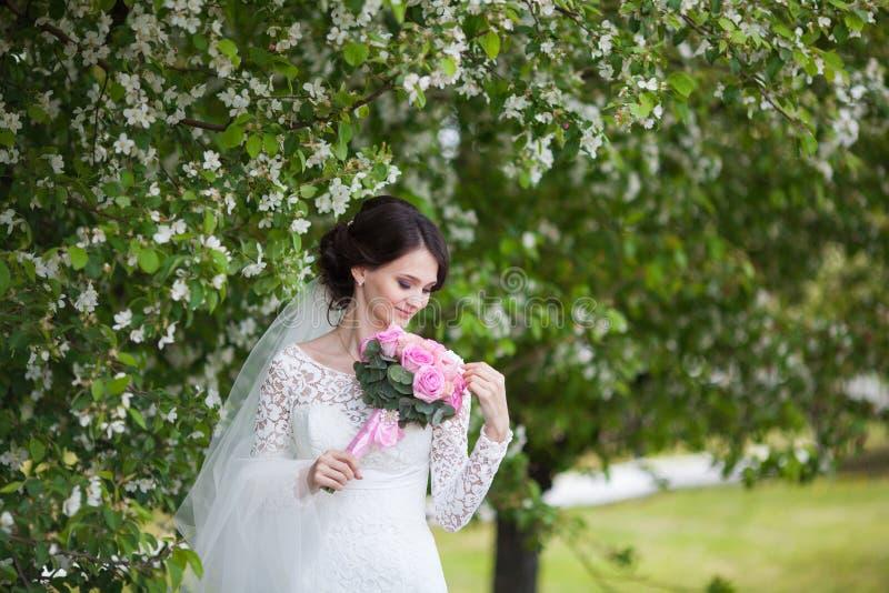 Jonge mooie vrouw, bruid met huwelijksboeket in bloeiende tuin stock afbeeldingen