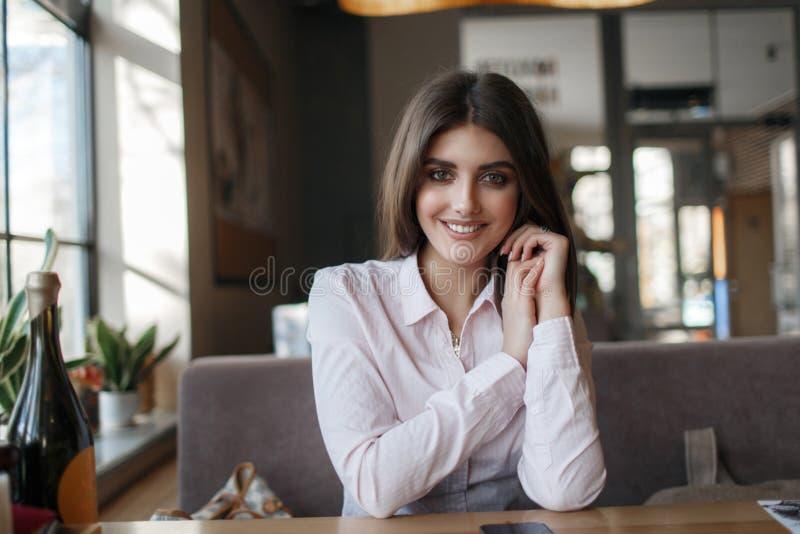 Jonge mooie vrouw, brunette, die alleen bij een lijst in een koffie zitten royalty-vrije stock fotografie