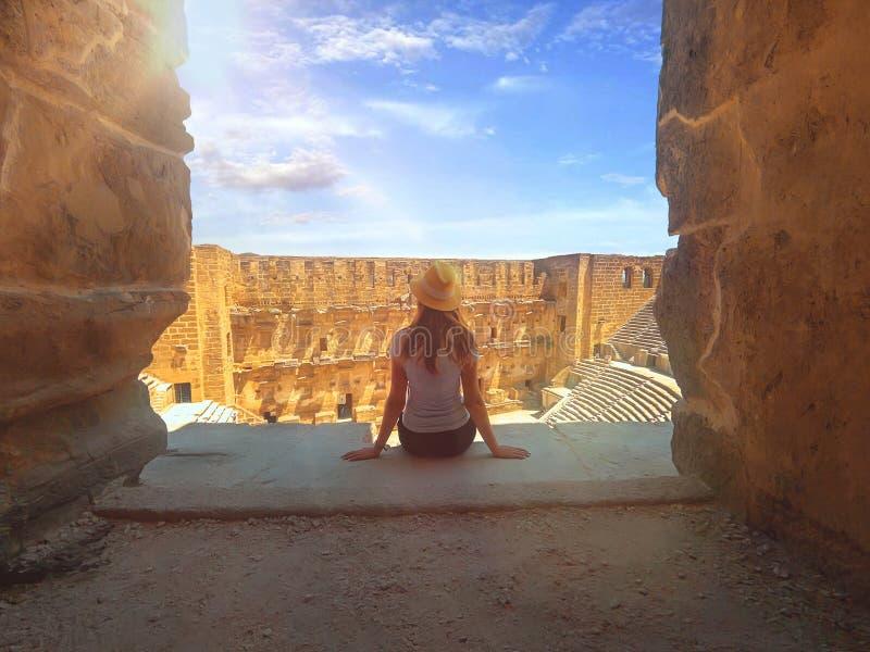 Jonge mooie vrouw in de hoed zit dichtbij en geniet van het uitzicht van Amphitheater Aspendos in de zomer stock foto