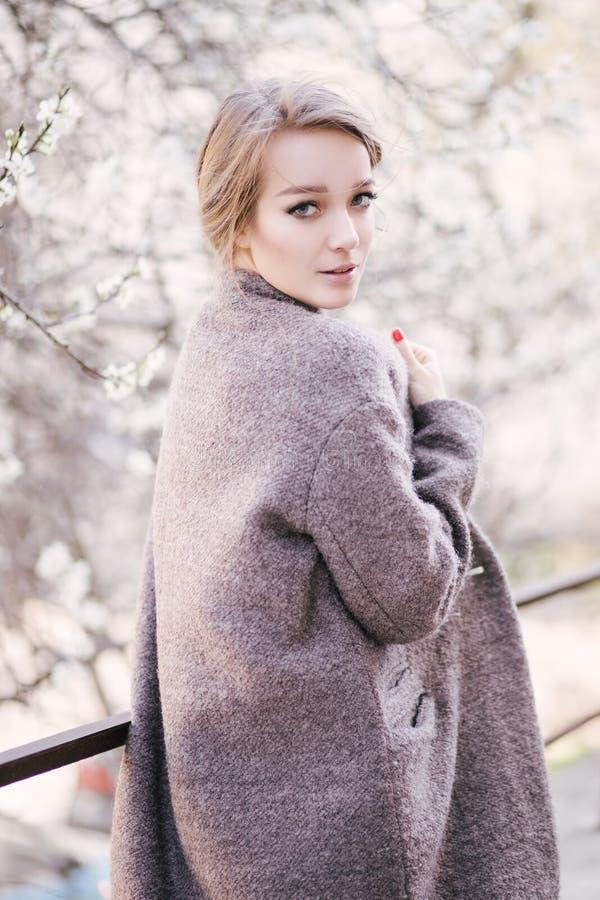 Jonge mooie vrouw dichtbij bomen in bloesem in de lente Verbindende haarstijl royalty-vrije stock afbeeldingen