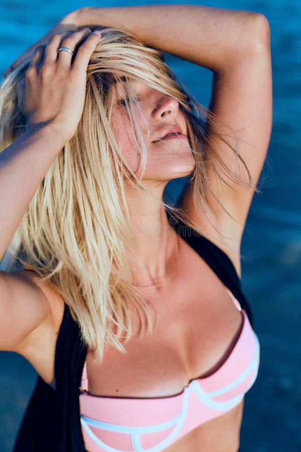 Jonge mooie vrouw dichtbij de oceaan op een de zomerdag stock foto