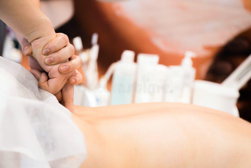 Jonge mooie vrouw die achtermassage in kuuroordsalon hebben Massagetechnieken royalty-vrije stock foto's