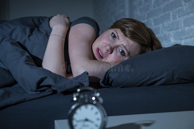 Jonge mooie vrouw die in bed laat bij nacht liggen die aan slapeloosheid lijden die aan slaap proberen stock afbeeldingen