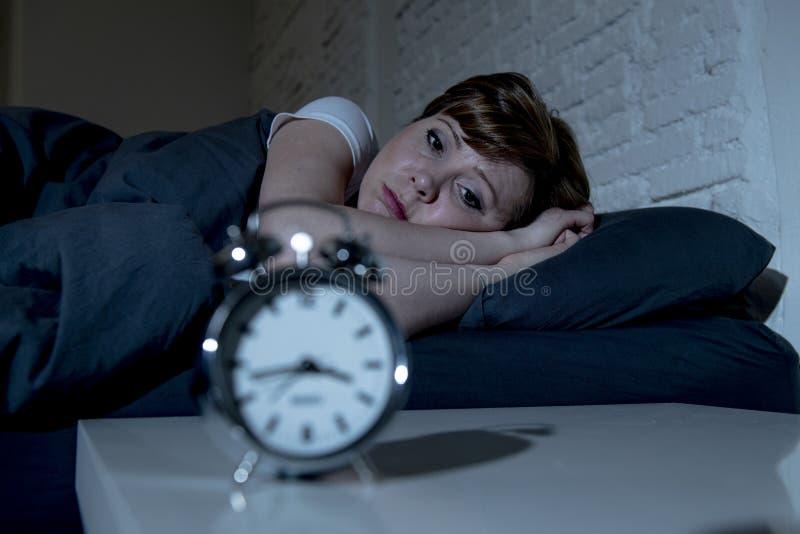 Jonge mooie vrouw die in bed laat bij nacht liggen die aan slapeloosheid lijden die aan slaap proberen stock afbeelding