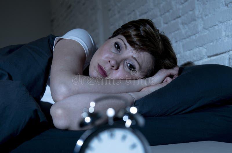 Jonge mooie vrouw die in bed laat bij nacht liggen die aan slapeloosheid lijden die aan slaap proberen stock foto's
