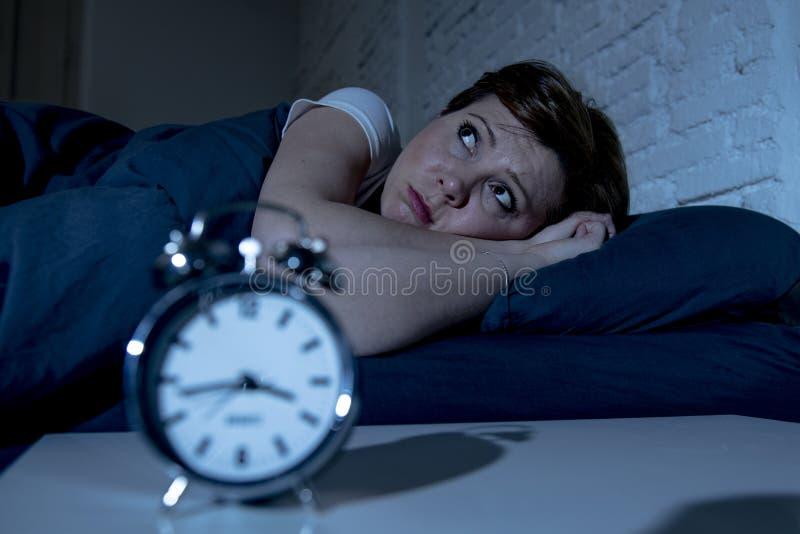 Jonge mooie vrouw die in bed laat bij nacht liggen die aan slapeloosheid lijden die aan slaap proberen stock foto