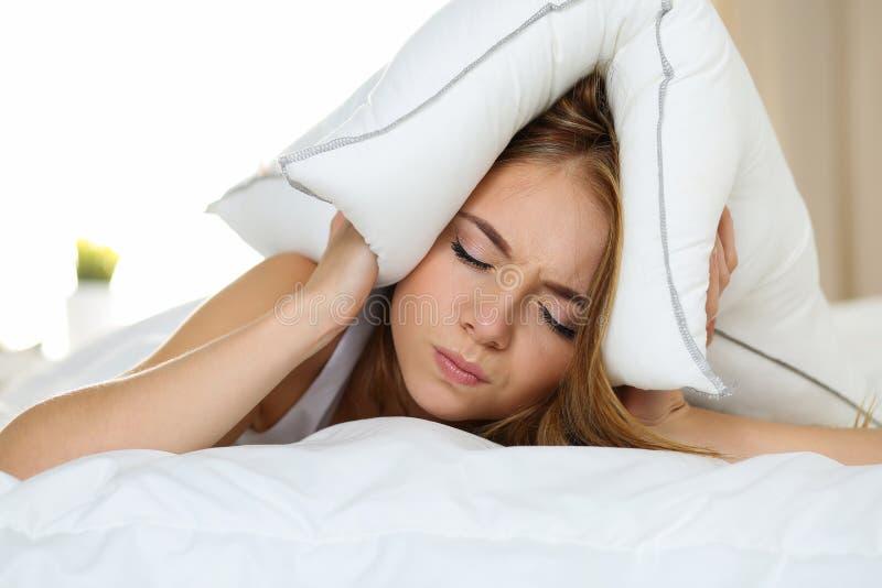 Jonge mooie vrouw die in bed liggen die met slapeloosheid lijden royalty-vrije stock foto