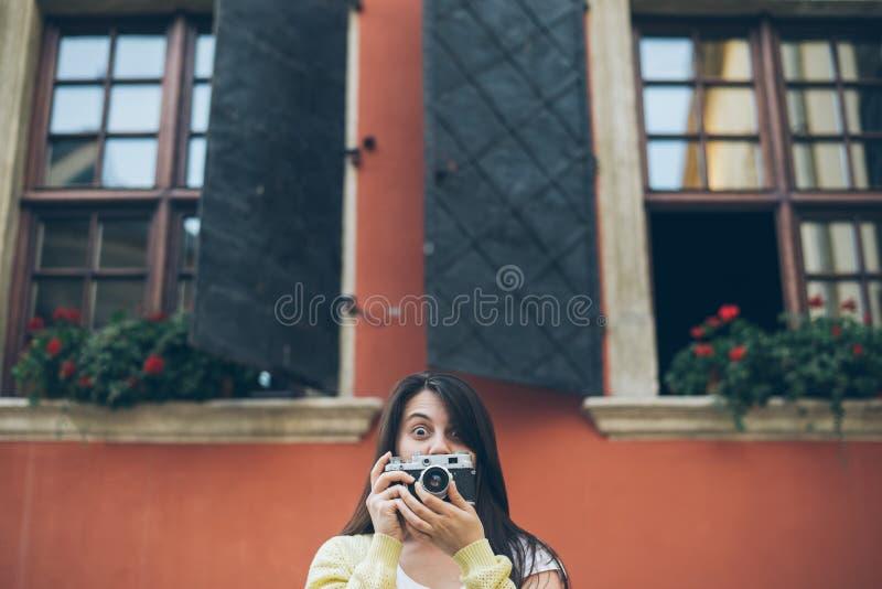 Jonge mooie vrouw die beeld met oude camera nemen stock afbeelding