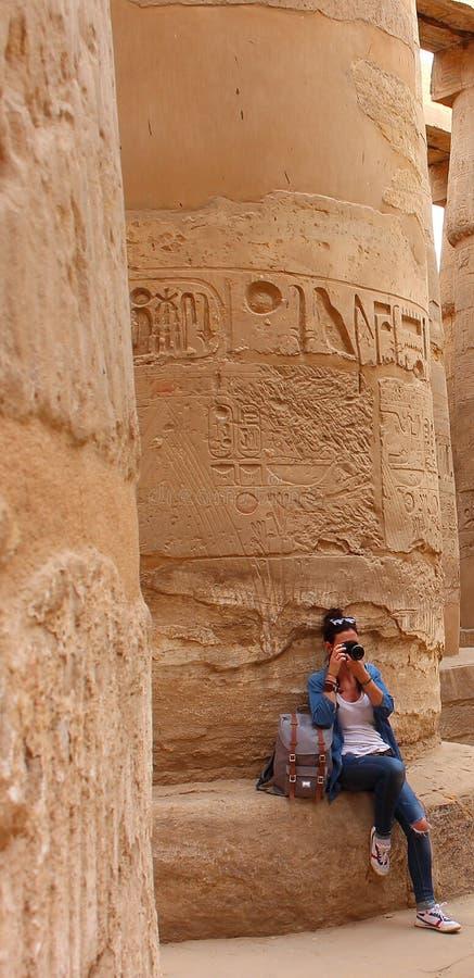 Jonge mooie vrouw die beelden nemen tussen de kolommen van de hypostyle zaal van de tempel van Karnak in Luxor stock afbeeldingen
