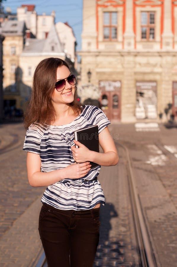 Jonge mooie vrouw die in de ochtendstad lopen met een boek stock fotografie