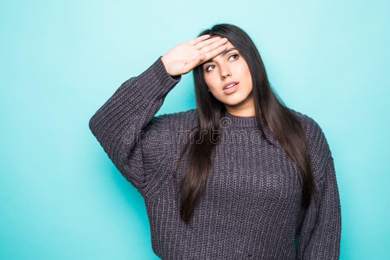 Jonge mooie vrouw die de wintersweater over geïsoleerde blauwe achtergrond dragen die aan wanhopig en beklemtoonde hoofdpijn lijd royalty-vrije stock afbeeldingen