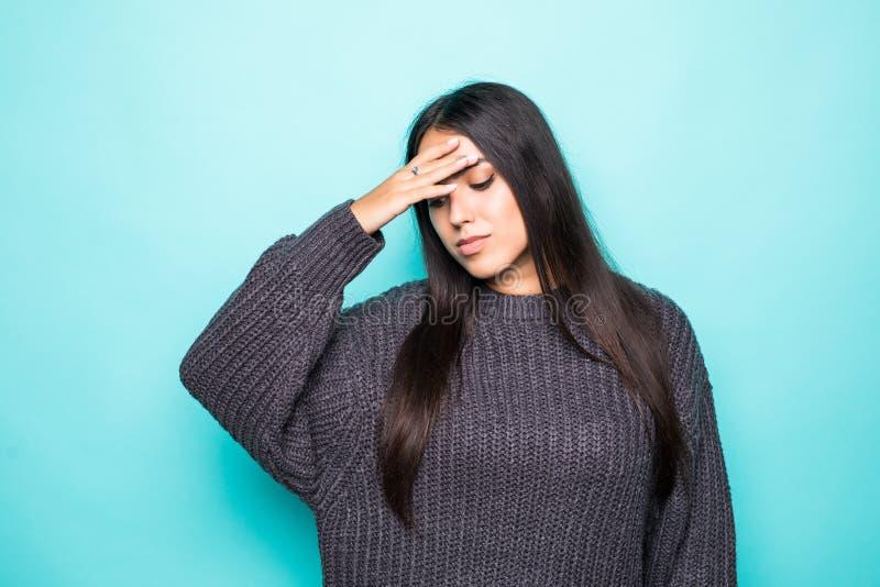 Jonge mooie vrouw die de wintersweater over geïsoleerde blauwe achtergrond dragen die aan wanhopig en beklemtoonde hoofdpijn lijd stock foto's