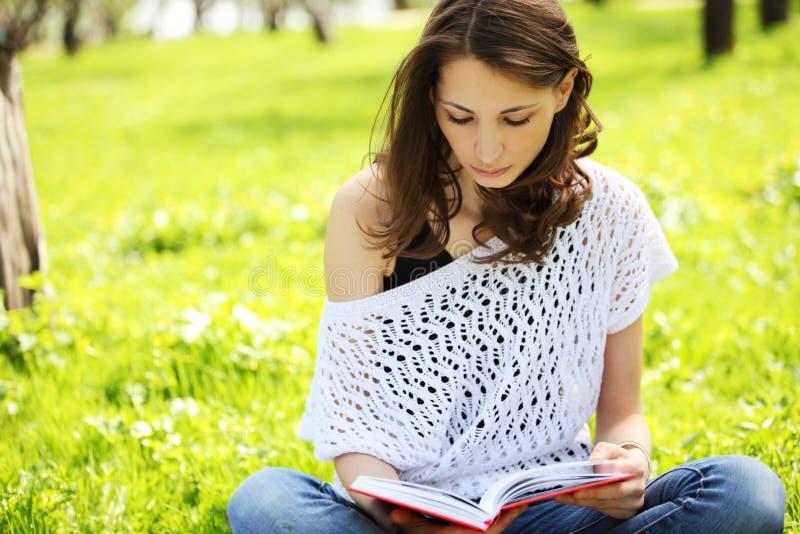 Jonge mooie vrouw die in de zomerpark een boek lezen stock foto's