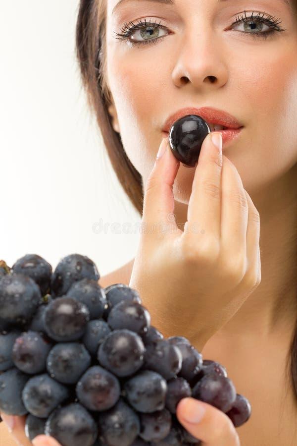 Jonge mooie vrouw die druiven eten royalty-vrije stock afbeeldingen