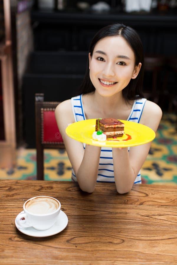 Jonge mooie vrouw die een dessert eten royalty-vrije stock fotografie