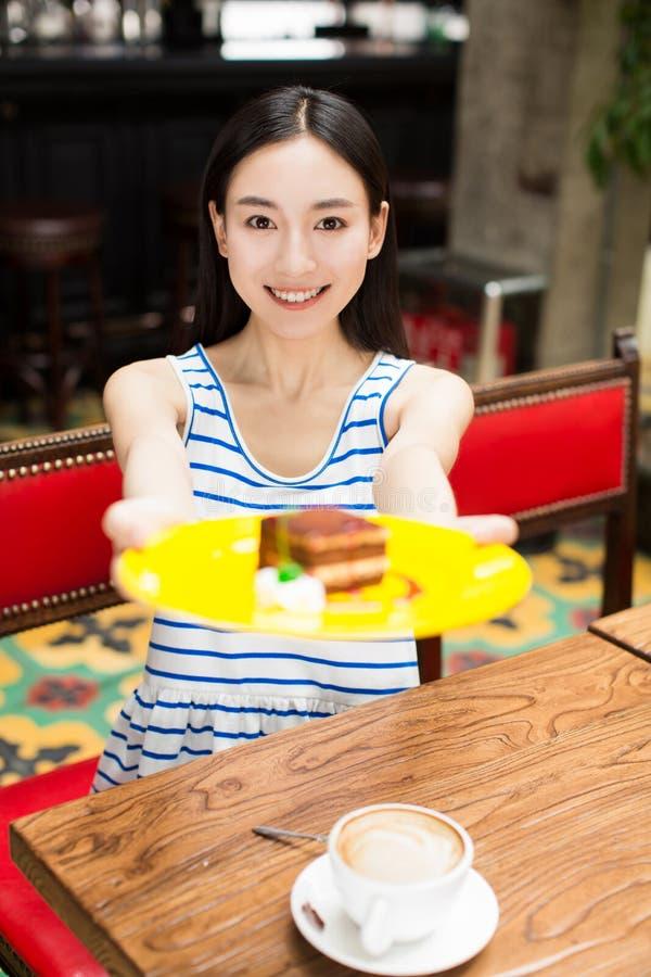 Jonge mooie vrouw die een dessert eten royalty-vrije stock afbeelding